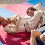 Judoka choking a man with her legs