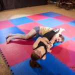 Akela applying headscissors with one of his arms trapped between her legs